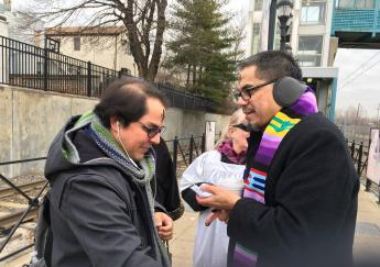 Father Greg distributes ashes to Armileo  De Mecano at light rail station